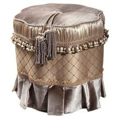 """Upholstered ottoman with a cord and tassel accent and pleated skirt.  Product: OttomanConstruction Material: Polyester and woodColor: Brown and taupeDimensions: 18"""" H x 13"""" Diameter"""