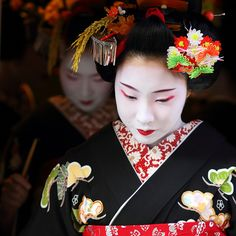 January 5th, 2012.  Kyoto, Japan. The maiko Fukumi and Fukumari. On this day geiko and maiko make their way round the tea houses of the Miyagawa-cho district to pay courtesy calls. They wear formal, black kimono and, until January 15th, an ear of rice in their hair, photograph by Michael Chandler.