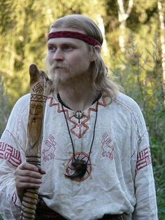 A Russian man wearing a medieval costume of the 9th century. The embroidery patterns of his shirt have a sacred meaning. Veles's face (a pre-Christian Slavic god) is carved on his walking stick. #medieval #Russian #history