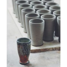 A board of recently thrown #ceramic beer cups, along with a lone finished tan glazed piece. I've made the #form a bit fuller on the bottom, the last batch I made were a little too narrow, like the fired cup here. These will be turned and hakame brushed after they've firmed up. #pottery #ceramics #liveauthentic #craft #craftsmanship #stoneware #clay #handmade #sodafired