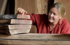 Jessica Wickham, 48, owner of WIckham Solid Wood Studio in Beacon, explains the variations in a stack of black walnut flitches, which are all cut from the same tree. Wickham selects hardwoods from the Hudson Valley for her furniture design business.