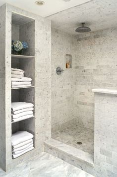 Sleek shower tile...Love the built-in shelving unit for towels!