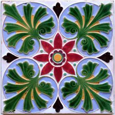An embossed majolica tile in rich colour tones with a quadruple leaf and flower head design in the Hispanic taste....