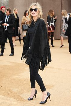 Kate Moss wearing a black cape with fringe, black cuffed jeans, and black pumps