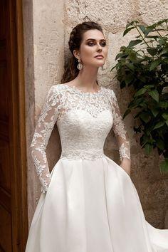 Закрытое свадебное платье с фактурными кружевными рукавами и скрытыми карманами в юбке.