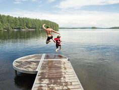 Father and Son Jumping in Lake, Belgrade Lakes, Maine, USA by Radius Images on 500px