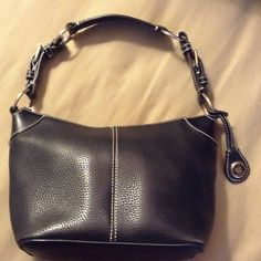 Dooney and Bourke Black Leather Purse Cute black leather Dooney and Bourke purse. The purse has a zippered pocket inside and a small pocket for a phone (it is not big enough for an iPhone).  There is also a small strap inside with a clasp for keys. Purse is in excellent condition except a small area where the stitching has come out (see picture).  This is from a smoke and pet free home. Dooney & Bourke Bags Shoulder Bags