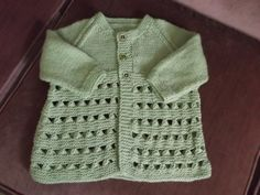 Delightful little matinee coat hand knit in a pistachio green yarn. Rows of stocking stitch and a twisted loop pattern gives a lace appearance to the coat. Fastens in the front with three pistachio green buttons. Actual measurements are: Chest 22 inches. Sleeve measured along seam 6 inches. Length from back of neck to hem 12.50 inches.