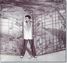 Elvis at his grand iron fence gateway at Graceland, his grand estate in Memphis, TN