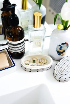 Inside Jewelry Designer Kathryn Bentley's Home: On the bathroom sink: vase filled with tulips, a dotted ring dish with cover, Aesop hand soap, and fragrance.   coveteur.com