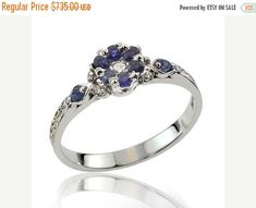 This is a beautiful dark blue sapphire diamond flower ring in 18k gold, that features one small diamond center point, with six sapphires substituting