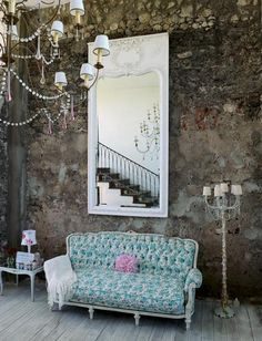 Muebles románticos, decapados y estampados con flores, sobre una pared de piedra.