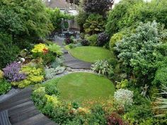 Pair of circular lawns in a small, densely designed garden.