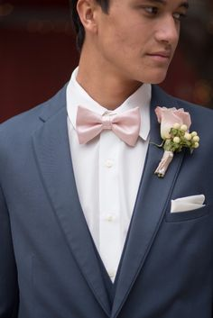 Blush pink bow tie and boutonniere with a slate blue suit.