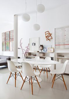 Clean modern dining room with Eero Saarinen table and Charles and Ray Eames molded chairs in the apartment in the center of old Madrid, designed by @isabelfrg.