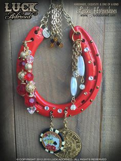 """""""OLD VEGAS LUCK"""" is a glossy red horseshoe with pieces of vintage Vegas style! Perfect for extra good luck! It has Swarovski crystals in copper and white diamond with vintage dangles reminiscent of th"""