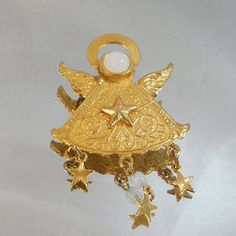 This #vintage angel brooch is just adorable!  It features a gold tone angel in flight with a moonstone face and dangling gold tone stars with a milky moonglow bead.  The cen... #ecochic #etsy #jewelry #jewellery
