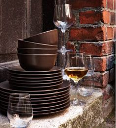 Brown stoneware bowls, side plates and plates shown together with glasses and wine glasses