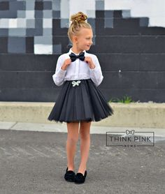 """Prepare to shine and shimmer in our """"All That Shimmers"""" BlackTulle Skirt! This skirt is embellished with a sparkly diamond bow on the soft satin waistband. Featuring 6 layers of the tulle that give the most beautiful silhouette,ease of movement and perfect for twirling.SIZES Small 1-3 yearsMedium 3-5 yearsLarge 5-7 years"""