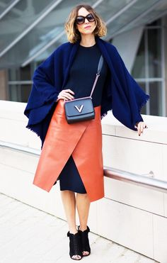 Candela Novembre wears a ribbed tank dress, orange leather skirt, peep-toe booties, a navy blue shawl, round sunglasses, and a crossbody Louis Vuitton bag