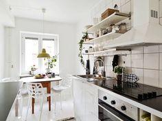 skandynawska kuchnia,biała kuchnia z drewnianym stołem,białe ażurowe krzesła przy drewnianym stole,plastikowe krzesła w kuchni,białe krzesła z tworzywa do jadalni i kuchni,modne krzesła w kuchni
