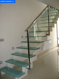 Barandilla acero inoxidable con cristal laminar transparente sobre escalera de hierro y peldaños de cristal