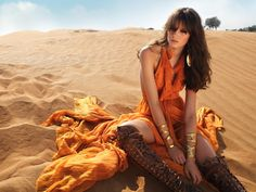 Love hardness pof the boots against the soft sand and orange dress. Great photo