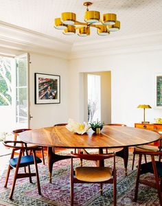 Modern dining space with gold light fixture, round wood dining set, and shell