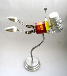 https://flic.kr/p/84Yuk2 | Firomatic 518 - 2 Found Object Flying Robot Assemblage Sclupture By Brian Marshall | Robot sculpture assembled from found objects by Brian Marshall - Wilmington, DE.  Items included in my sculptures vary from vintage household kitchen items to recycled industrial scrap.  Some of my favorite items to use are old oil cans, aluminum measuring spoons, electrical meters, retro blenders, anodized cups, and pencil sharpeners.
