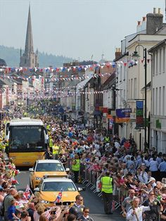 Huge crowds gather to see Torchbearer Kelvin Perrett carry the Olympic Flame on the Torch Relay between Monmouth and Raglan.