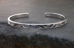 Solid sterling cuff bracelet. Hand engraved with bright cuts in a running vine pattern. This style of engraving is rapidly becoming a lost art. Handmade by Sierra Silversmiths. $50