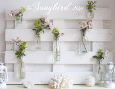 Summer mantel with pallet wood and flowers in bottles
