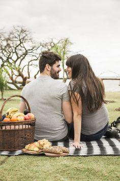 Cesta de picnic y pan horneado frente a una pareja joven mirando el uno al otro Foto gratis