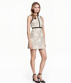 Kurzes, figurbetontes Kleid aus Jacquardstoff mit dekorativen Kontrastborten. Ärmelloses Modell mit seitlichen Nahttaschen und einem verdeckten Reißverschluss im Rücken. Gefüttert.