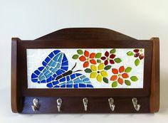 Porta chaves em imbuia, com mosaico em pastilhas de vidro e cristal, com flores recortadas manualmente e uma borboleta azul da Mata Atlântica. <br>Um lindo e sofisticado objeto para organizar suas chaves e suas correspondências ou receitas, ou contas a pagar, ou o que você quiser deixar em ordem e à vista. Um presente que agrada a todos! <br> <br>Tamanho: 27 cm de largura x 17 cm de comprimento