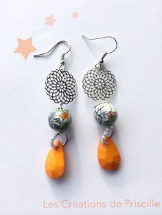 Boucles d'oreilles percees, estampes rosaces argentées, perles résines motifs fleuris, breloques gouttes orange  Perles de rocailles sur l'anneau   Longueur des BO: 6cm enviro - 12137185