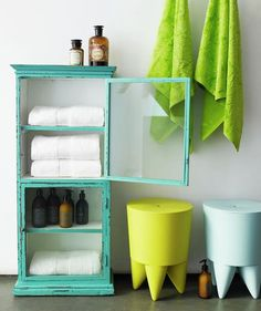 Bright and cheery accents can transform a white bathroom. This vintage storage cabinet in vibrant turquoise pairs well with stools in invigorating hues of lemon and baby blue.