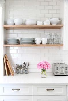 White subway tiles in kitchen with open shelves and white dinnerware