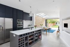 High Barnet Terrace House Transformation: modern Kitchen by Model Projects Ltd Understairs Storage Space, Storage Spaces, Corner Shower Units, Cooking Company, Single Storey Extension, Large Open Plan Kitchens, New Staircase, Roof Panels, Folding Doors