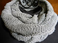 Infinite possibilities in a hand knit gray and silver infinity scarf.  Long enough at a 72 inch diameter to wear long, wrap at least three times, knot, twist and more. The infinity scarf is very soft and drapes well. I knit this 7 inch wide scarf in a reversible pattern so there is no right or wrong side.
