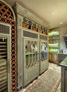 Sub-Zero refrigerators with antique French cabinet look, and terra-cotta pipe tiles stacked for wine bottle storage surrounding glass front wine refrigerator... Love the built-in plate rack, too.