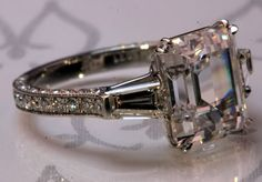 Beautiful Leon Mege Antique feel asscher. Center is a J, so also warm, has a clean look but the pave shank with milgrain gives it a bit of a romantic, antiquey feel.