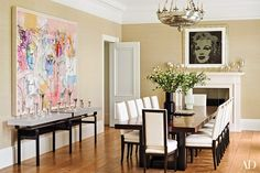 In the dining room, a work by George Condo is displayed over a Lucite-and-bronze console by Eric Appel, while an Andy Warhol silkscreen is mounted above the fireplace | archdigest.com