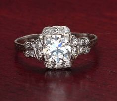Art Deco Diamond Engagement Ring. An Old European Cut diamond weighing 1.30 cts and certified by the GIA as K color and VVS2 clarity (report#2155617721) is set square within a frame of single cut diamonds. An additional eight single cut diamonds are set in double rows in the shoulders (total 18 diamonds = 0.28 cts, GH color and SI clarity) and the band has a softly worn, hand engraved design. A vintage original c. 1930. Platinum Size 9. Resizing is possible, please inquire.