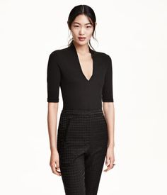 Short-sleeved bodysuit in ribbed jersey with a slight sheen. Stand-up collar at back of neck tapering into a low-cut V-neck at front.
