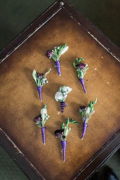 Boutonnieres with purple ribbon, tiny roses, and wintery greens | A Day In May, Event Planning & Design | Northern Michigan Weddings | Traverse City Weddings | Wed in a Winter Wonderland | Grand Traverse Resort and Spa | Blaine Seisser Photography