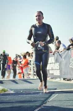 out of the water and into transition with a blue seventy wetsuit