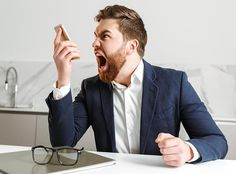 Buy Portrait of an angry young businessman by vadymvdrobot on PhotoDune. Portrait of an angry young businessman dressed in suit yelling at mobile phone while sitting at the table indoors