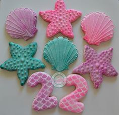 Sea shell cookies~                          By SugarySweetCookies, Glittery, sparkly sea life set!Perfect cookie set for that special little lady in your life.Sweet cookie set is expertly decorated and freshly made just for you.Set comes with:-4. Pink, purple, teal Seashells-4.Starfish-4.Matching NumbersPick up to 3 colors. Each cookie comes individually sealed and wrapped for max freshness and protection.