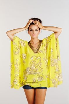 Fold a pashmina in half. Sew halway up each side. Cut out a neckline. Sew on lace or decorative trim.
